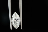 1.5 carat diamond held with tweezers on black background poster