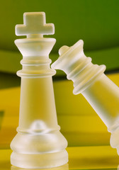 king and queen chess coins on green and yellow background