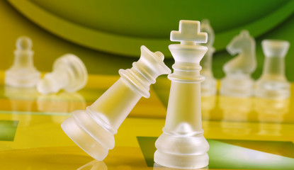 Chess coins on green and yellow background chess board