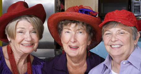 Three Senior Women Wearing Red Hats