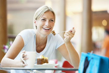Woman Eating A Piece Of Cake At The Mall