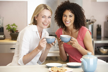 Female Friends Enjoying Tea And Cookies At Home