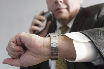 Businessman checking time and using an electronic shaver.
