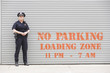Woman police officer standing in front of a parking zone.