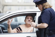 Woman police officer checking driver's license.