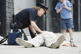Woman police officer administering first aid to a senior man.