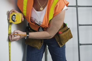 View of a woman using tape measure.