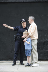 Woman police officer directing a senior man with a boy.