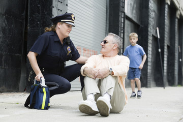 Woman police officer talking to a senior man.