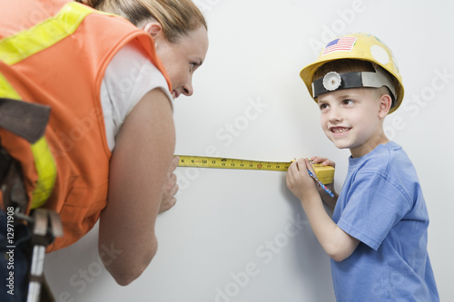 View of a woman and boy measuring wall with tape measure.