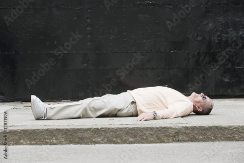 Senior man lying on a road.