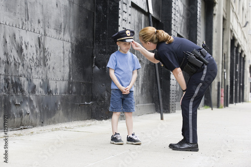 Woman police officer talking to a boy.