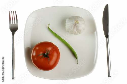 Plate with tomato green bean and garlic. Isolated on white.
