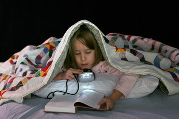girl reading in bed with a book light