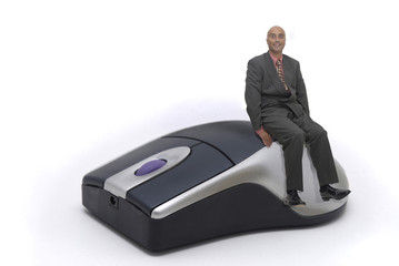 Businessman siting on a mouse isolated in white