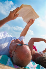 Mature couple reading on beach.
