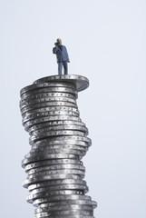 Businessmann auf Geldstapel