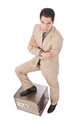 Geschäftsmann stützt sich auf einen Tresor, arme verschränkt