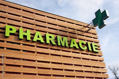 Leinwanddruck Bild Enseigne pharmacie sur un bâtiment en bois