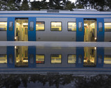 Commuter train reflected in a puddle. poster