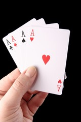 Female hand with playing cards isolated on black