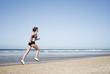 Junge Frau joggt am Strand