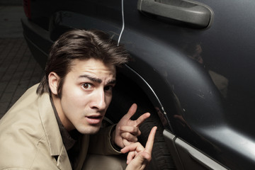 Young man upset at the dent in his car