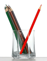 Crayons in a glass, red one is leaned against the others