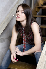 young attractive smoking  girl in jeans having a hole sitting on
