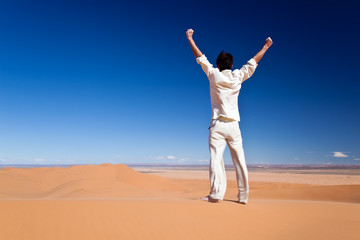 Success concept: man at the top of a sand dune