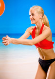 Young woman in sportswear playing with ball on beach poster