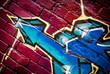 Arrow: Graffiti detail on a textured brick wall