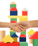 mother holding hand of son, toy tower background