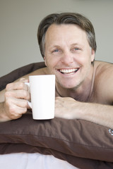 man drinking coffee in bed.