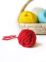 hank of the yarn for knitting in basket, focus on red hank