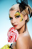 Young beauty with butterfly face-art heart shaped lollypop
