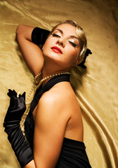 Lovely woman on golden fabric retro portrait