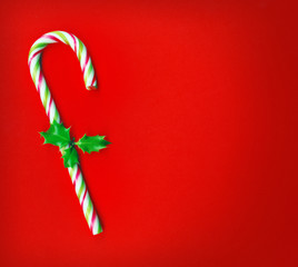 Candy cane with  holly leaves on red background, candy cane