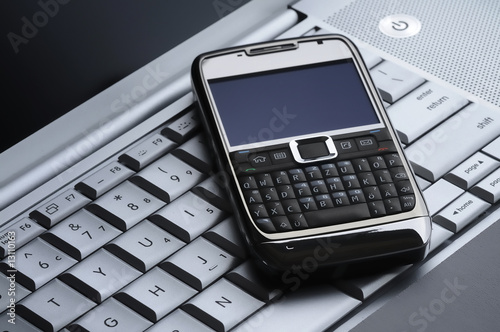 cell phone on a silver laptop keyboard