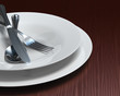 Clean white dishes & cutlery on dark woodgrain table