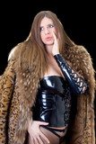 Beautiful young lady in latex suit and a fur coat poster