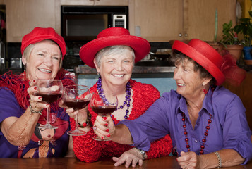Three red hat ladies toasting with wine