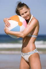 Junge Frau mit Wasserball am Strand