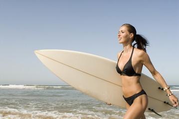 Junge Frau mit Surfboard am Strand