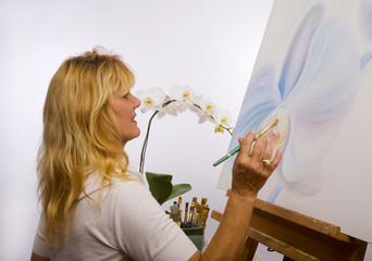 A female artist painting orchids on canvas in her studio