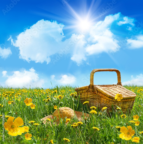 Summer picnic basket with straw hat in a field of flowers