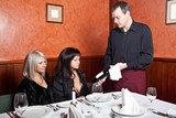 The waiter shows a bottle of wine visitor to the restaurant poster
