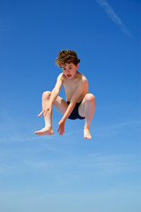 Boy jumping against ble sky