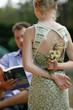 fille cachant des fleurs derrière son dos