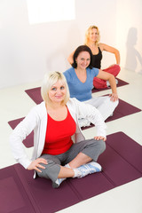 Women sitting cross-legged on mat